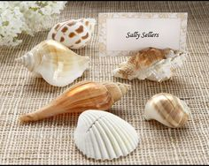 Shell Wedding Place Card Holder Set includes six place card holders. They are real seashells so each one will be unique. They have beautiful color and a shiny finish for a touch of elegance. They have a slit in the top to hold a place card.