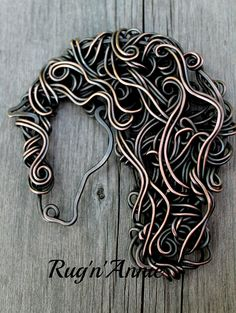 """Lilly"".  Double pronged horse head, pin/brooch.  Copper wire with stainless steel prongs."