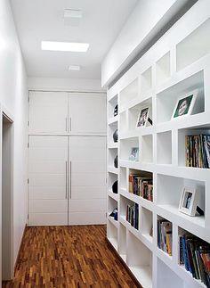 Bom aproveitamento de um corredor, com uma estante com nichos, que abrigam livros, objetos de decoração, lembranças de viagem, fotografias, etc.