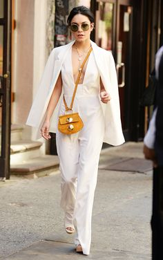 Vanessa Hudgens in a white blazer, white jumpsuit, white heels, yellow bag, and sunglasses