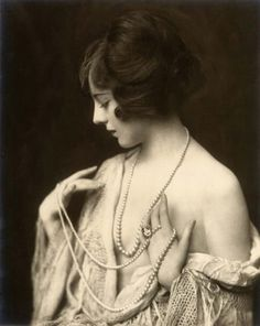 The model has feminine hands which makes her look fragile as the pearl necklace drapes around her fingers. This is a soft and delicate pose.