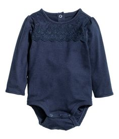 Dark blue. Bodysuit in cotton jersey with a lace yoke at front and long puff sleeves. Snap fasteners at back of neck and at gusset.