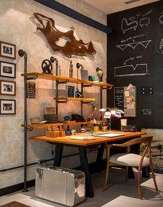 Repare que a estante criada por Emmília Cardoso é formada por pranchas de madeira e suspensa por ferros de tubulação de água