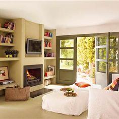Salón en tonos verdes con librería a medida, chimenea, televisor y sofá blanco_00336225