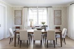 Clean lines and exceptional materials are exhibited in the home's dining room, where refined tufted dining chairs by Baker line up uniformly beneath a walnut Holly Hunt table. On the walls, Holland & Sherry curtains blend seamlessly with Pierre Frey wallpaper.