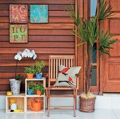 Uma composição com três nichos de madeira resultou na miniestante que apoia uma bela orquídea. Há lugar, ainda, para vasinhos de tempero e itens de jardinagem, como rastelo e regador. O acabamento rústico dos quadros e os retalhos que estampam a capa da almofada reforçam a atmosfera campestre.