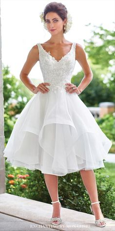 Sleeveless tulle and organza knee-length full A-line dress with hand-beaded lace V-neck bodice, illusion lace back with covered buttons, asymmetrically tiered and layered skirt with horsehair trim.