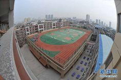 A newly built sports ground on top of a three-floor teaching building of Nanmen Middle School in Putian, South China's Fujian province on Nov 27, 2012. The sporting arena, surrounded by over four-meter high guard bars, includes three basketball courts, two volleyball courts. The $4.8 million investment was built on the top of building due to a lack of space as the school is situated in the downtown of the city.