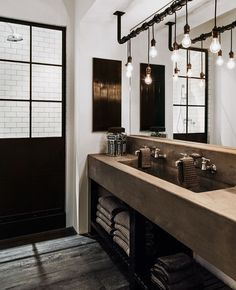 Exposed Hanging Light Bulbs in industrial bathroom with concrete sink via Delish Diane Keaton