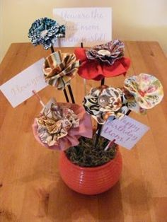 Gathered fabric hot glued into spiral, button in center.  Hot glued onto dowels.  Clothes pin on dowel to hold notes.