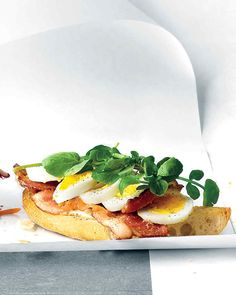 A sliced hard-boiled egg, crispy bacon, and peppery watercress top off this open-faced take on a breakfast sandwich.