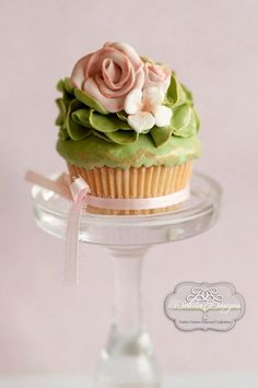 A green ruffled decorated cupcake adorned with simple flowers.