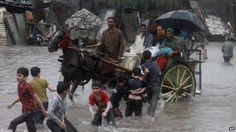 People make their way through a flooded road caused by heavy rain in Lahore, Pakistan, 5 September 2014