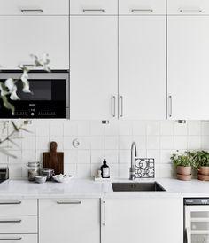 Modern, white kitchen in a Scandinavian styled Gothenburg apartment.