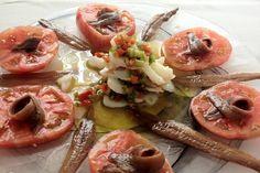 Ensalada de tomate con ventresca de bonito del Norte laminado y salsa vinagreta acompañado por anchoas del Cantábrico.