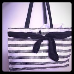 NWOT black and white strapped tote with bow Never used. Velcro closes. 1 small inside pocket. Satin bow. Weaving is almost like a basket weave Bags Totes