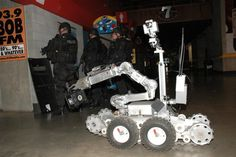 The Tactical Robot in this picture is called the Remotec Andros F6A. Its main function is for explosive disposal, however it is also capable of delivering various items required in tactical operations such as a negotiator throw phone (as seen in this photo),as well as food and beverage. It also has a remote surveillance capability.