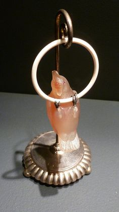 Fabergé gemstone parrot. Carved agate parrot with ruby eyes and gold feet hangs from a carved ivory ring.