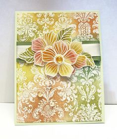 I've used the Transparent set Petal Party for this card, as well as the Slapstick stamp delicate pattern.  I stamped all the images in VersaMark and heat embossed with white embossing powder.  I added color by using one of the pads that attaches to the distress ink applicator without the applicator.  I find I have more control applying the distress inks in that manner.  I arranged the three flower images, using some pop dots. I applied dew drops for the flower centers and a few at random on…