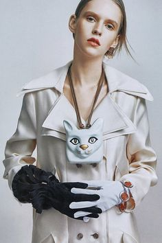 LOEWE's Fall Winter 2016 look: Cat Head Necklace in white, double lapel trench in champagne and black and white latern gloves featured in Figaro Japan