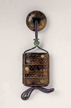 Inro, Ojime, Momoyama period, 16th-17th century  Costume/clothing accessory/waistwear, Four-case inro with design of twenty horizontal patterns in black and gold hiramakie, red nashiji and metal emblems; malachite vase ojime