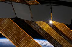 The sun shines through a truss-based radiator panel and a primary solar array panel on the Earth-orbiting International Space Station (ISS) ...