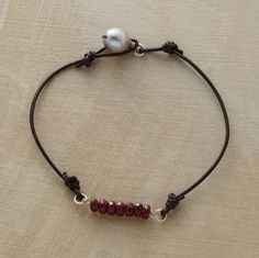 """RUBY RIATA BRACELET--Seven rubies align on sterling silver lassoed in by leather cord. Luminous cultured freshwater pearl and loop closure. Exclusive. Handcrafted in USA. Approx. 7""""L."""
