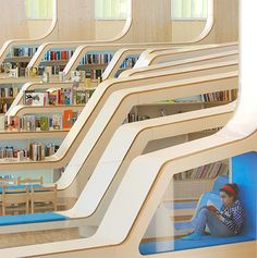 Beautiful public library designed by Helen & Hard Architects located in the downtown of Vennesla, Norway | Unique interior of the Vennesla Library and Culture House consists of 27 wooden ribs that form bookshelves and comfortable reading benches | Large windows let in plenty of light and provide beautiful views