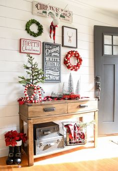 A beautiful and classic Christmas entryway and living room featuring shades of red, green and black.