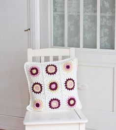 I like the idea of a granny square crocheted pillow with mostly white - pops of color - scalloped border