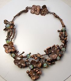 Terry Gates - Fossil Ammonite, moonstone or dichroic glass cabochon, electroformed shell, micro-beads, CZ's, copper foil, copper wire, conductive paint, glue, miscellaneous polished rocks, sealed plant material, and a tutorial containing detailed instructions and photographs. Bead Elements and Design Show