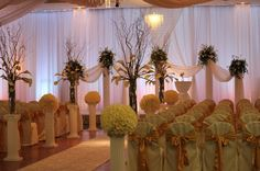 indoor ceremony - White pipe and drape behind the bride and groom to make the stage more intimate.