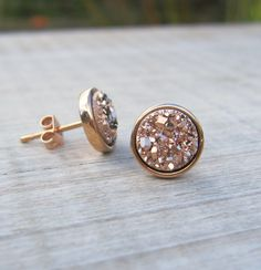 These stunning 8mm studs were made using the highest quality natural rose gold druzy stones. Druzy is the glittering effect of tiny crystals over top a colourful mineral. - this gives a stunning multifaceted surface to each earring which glints, glistens and catches the light. Each druzy is mounted in a rose gold plated bezel cup for a touch of luxury.  What I love most about these druzy studs is that they are gorgeously glitzy whilst remaining a classy earthy element. They are perfect to…