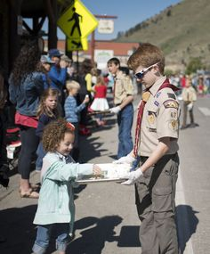 Tom Salerno of Boy Scout Troop 67 hands out lemon bars to spectators at the annual parade, which culminated at Town Square.