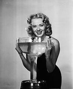 Everything grows large in California, they say! The beautiful 1950 Vintage Queen has the proof, as she playfully prepares to drink a giant glass filled with California Champagne.