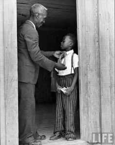 Sharecropper Lonnie Fair helping his son dress in preparation for Sunday church services - Photograph by Alfred Eisenstaedt. Scott, Mississippi,1936.