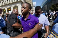 A Philadelphia McDonald's worker is cuffed by police during Thursday's strikes.