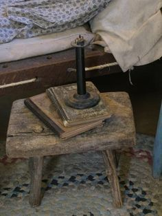 Primitive early wood bench, old school books, antique candle stick and hired mans rope