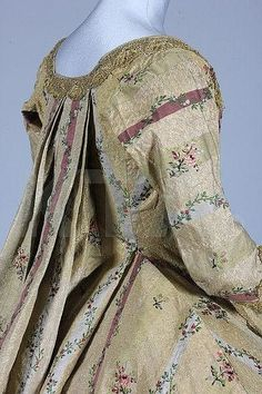 Detail side view, robe à la francaise, Italy or Spain, c. 1770. Gold brocaded striped silk, woven with puce and silver bands within the textured cloth of gold stripes, pretty floral sprigs and trails, edged and trimmed with scalloped gold bobbin lace. Lined in ivory taffeta.