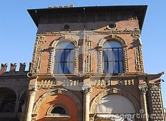 Photo made at an ancient palace in the center of Bologna in Emilia Romagna (Italy). The picture shows the facade, illuminated by the sun of a winter day under a deep blue sky, where there are twice a semicircle of which the right one with the white tent has a porch. On the first floor there are two large arched windows.