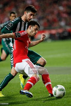 Benfica's forward Pizzi (F) \vies for the ball with Setubal's midfielder Ruca (B) during the Portuguese League football match between SL Benfica and Vitoria Setubal at Luz Stadium in Lisbon on April 18, 2016.