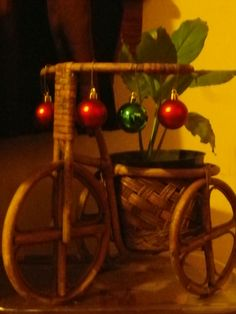 Christmas Decorations - Home and Garden - Adorable wooden tricycle with a peace lily in the basket and Christmas ornaments hanging form the handlebars. Peace, Love and Cycling!