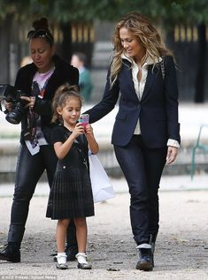 Tech savvy: Emme was engrossed with something on her heart covered iPhone. Pictured with mum Jennifer Lopez.