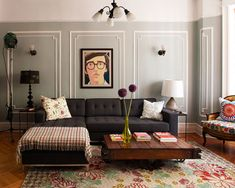 Light grey walls, dark grey couch & mixed colors.