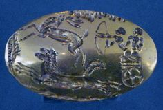 Gold seal-ring from grave 4 in Grave Circle A. The bezeal is 3.4 cm in length. The design represents two men in a chariot hunting a stag.
