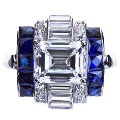 Exquisite deco styled diamond and sapphire set platinum ring with 2.15 carat emerald shape F color VVS1 clarity diamond center stone.  Contains straight baguette and brilliant round accenting stones with french-cut calibrated sapphires. USA, 20th century