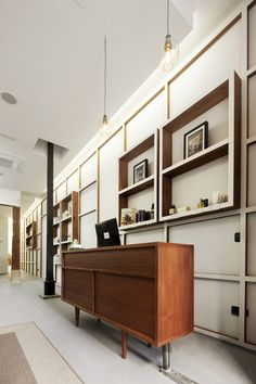 Salón Alberto Cali (Madrid) El mostrador de la entrada. Tras él, un panelado que reinterpreta las clásicas boiseries Blanco y madera | Galería de fotos 4 de 22 | AD