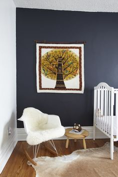 Fun boy's nursery design with dark blue accent wall, white vintage crib, cowhide rug and Eames Molded Plastic Rocker.    [paint blues]  Behr Poppyseed