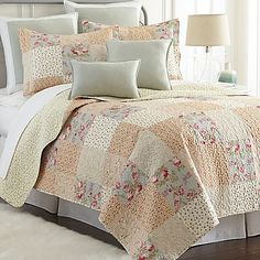 Wrap yourself in heirloom charm with the Riverside Reversible Mini Quilt from Sherry Kline. Adorned in a delicate patchwork of florals, this classic set boasts a blossomy mint green reverse, invoking warm feelings of a country cottage.