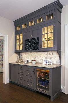 Concealed behind this elegant storage unit is everything you need to host the perfect party! It houses everything from liquor, different types of glass, and small items like wine charms, napkins, corkscrews, etc. The under counter beverage cooler from Sub Zero is a great way to keep various beverages at hand! You can even store snacks and juice boxes for kids so they aren't under foot after school! Follow us and check out our website's gallery to see the rest of this project and others!